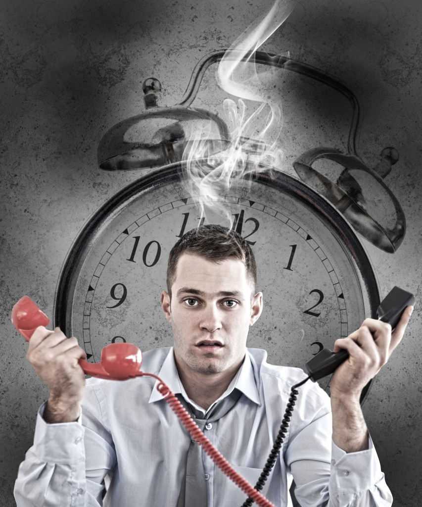 Business man stressed out by deadline holding two phone with smoking alarm clock in background